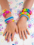 Childs arms wearing multicoloured bracelets. Colourful elastic loom band bracelets worn on  a child hands  against a white table top Stock Image