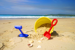 Childs beach bucket and spade on a sandy beach wit. A childs beach toys and seashells lying on a beautiful sandy beach during summer Royalty Free Stock Images