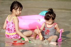 Childs on the beach. 2 childs play with sand on the beach stock image