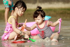 Childs on beach. 2 Childs play with sand on sea stock images