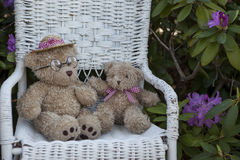 Childs bear on wicker chair with US Flag. Childs toy bears and US flag resting on a white wicker chair Stock Photo