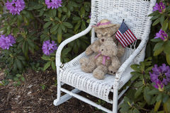 Childs bear on wicker chair with US Flag. A childs toy bear and US flag resting on a white wicker chair Royalty Free Stock Photos