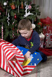 Childs Christmas. Child opening presents near the Christmas tree, Holiday has finally arrived Royalty Free Stock Image