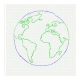 Childs dra av planetjorden på en anteckningsbok le Arkivbild
