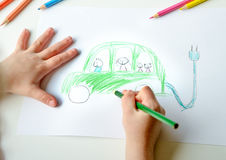 Childs drawing of eco-friendly car. Close-up of childs hands drawing a green electric zero emission car royalty free stock image