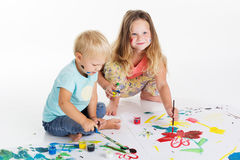 Childs está dibujando por las pinturas de la acuarela en el papel Imagenes de archivo