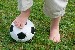 Childs Füße auf einem Fußball lizenzfreie stockfotos