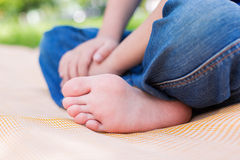 Childs foot. Foot of seated child on picnic or yoga. Selective focus royalty free stock image