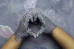 Childs geschilderde handen die een hart over een geschilderde houten branding simuleren Stock Foto