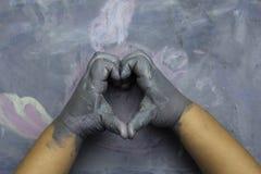 Childs geschilderde handen die een hart over een geschilderde houten branding simuleren Royalty-vrije Stock Fotografie