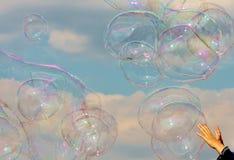 Childs händer når för bubblor som svävar på brisen i himlen Arkivbild