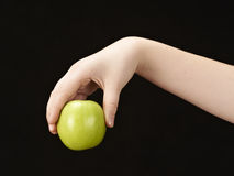 Childs hand with apple. Black background Royalty Free Stock Photos