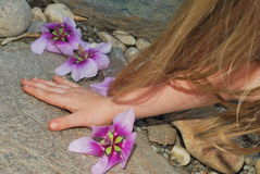 Childs Hand and Hair Touching Natural Rock. Pink, purple flowers on natural stone with a hand and a golden hair of a child Stock Images