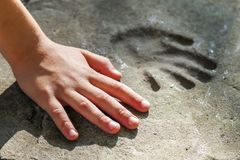 Childs hand and memorable handprint in concrete Royalty Free Stock Photo