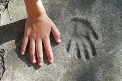 Childs hand and memorable handprint in concrete.  stock photo