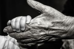 Childs hand and old wrinkled skin palm finger. Concept idea of love family protecting children and elderly people grandparent friendship togetherness Stock Images