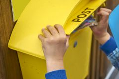Childs Hand Puts Blank Postcard in An Italian Yellow Post Box Pi royalty free stock images