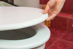 Childs hand puts the toilet seat Royalty Free Stock Photos
