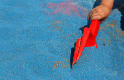 Childs hand with sand shovel. Childs hand holding red sand shovel in sandpit with blue sand Royalty Free Stock Photos