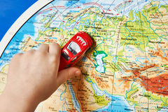 Childs hand with toy car on map of Eurasia. Childs hand with a toy car on the map of Eurasia Royalty Free Stock Photo