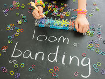 Childs hand using a band loom on a blackboard with Royalty Free Stock Images