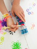 Childs hands with band loom, croche hook and multicoloured elast. Childs hands hooking colourful elastic loom bands with a croche hook on a band loom against a Royalty Free Stock Images