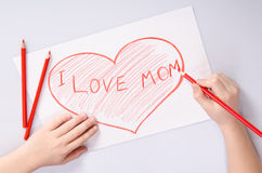 Childs hands drawing a heart that says I love mom Royalty Free Stock Photography