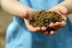 Childs hands with handful of earth Stock Photos