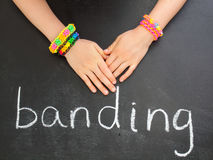 Childs hands with loom band bracelets on a blackbo Royalty Free Stock Images