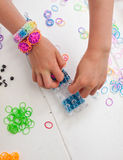 Childs hands with loom and multicoloured elastic bands Royalty Free Stock Photography