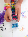 Childs hands with loom and multicoloured elastic bands Stock Photography
