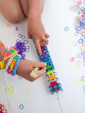 Childs hands with loom and multicoloured elastic bands Stock Photos