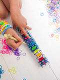 Childs hands with loom and multicoloured elastic bands Royalty Free Stock Photo
