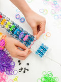 Childs hands with loom and multicoloured elastic bands. Childs hands placing colourful elastic loom bands on a band loom against a white table top Stock Images