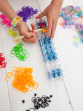 Childs hands making a bracelet on a band loom Royalty Free Stock Photo