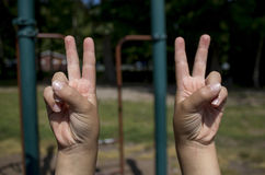 Childs hands making peace signs Stock Images