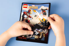 Childs hands open comic book Lego Marvel Super Heroes. Tambov, Russian Federation - January 12, 2015 Childs hands open comic book Lego Marvel Super Heroes. Blue royalty free stock photos