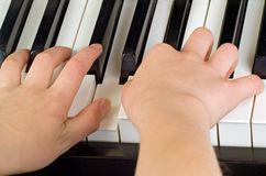 Childs hands playing the piano Royalty Free Stock Images