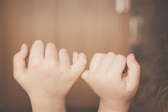 Childs hands promise isolated. Childs hands promise indoor in brown tones, isolated Royalty Free Stock Photo
