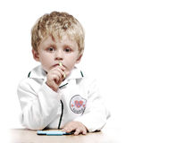 Childs health concept. Little boy dressed as a doctor with a serious expression Royalty Free Stock Photo