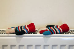 Childs knitted gloves drying on heating radiator after winter da Royalty Free Stock Image
