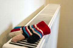 Childs knitted gloves drying on heating radiator after winter da Stock Image