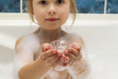 Childs little girls hands in bath with soap bubbles in it. Hygie. Ne concept Stock Photos
