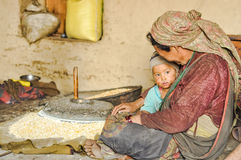 Childs look in Nepal. Dolpo, Nepal - circa May 2012: Native woman with headcloth sits on ground with child near stone hand grain mill in Dolpo, Nepal Stock Photos