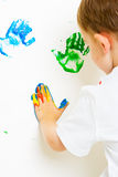 Childs messy painted hands on the wall Stock Image