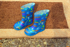 Childs over boots on a door mat. Royalty Free Stock Image