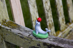 A childs plastic toy seal with a ball that was left on the arm of a public bench Royalty Free Stock Photo