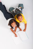 Childs play. Overhead view of two happy children drawing and reading books Royalty Free Stock Photos