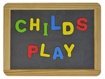 Childs play in colored letters on slate Royalty Free Stock Photography