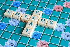 Childs play game tiles spelling. Photo of scrabble tiles game board spelling the words childs play royalty free stock image